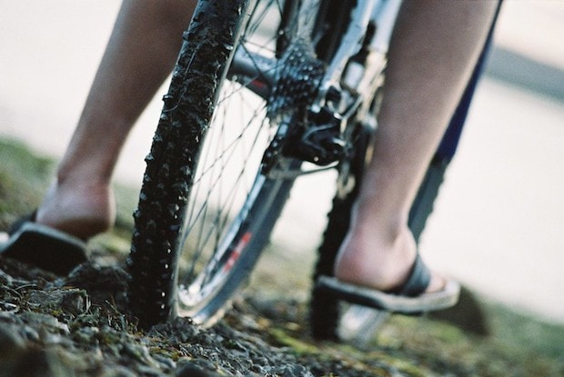 Close up of feet reaching to the ground on either side of a bike