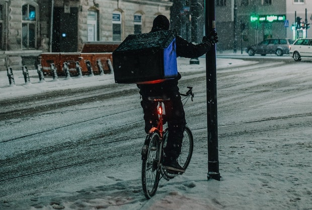 Cyclist holding a lamppost with a bike light on