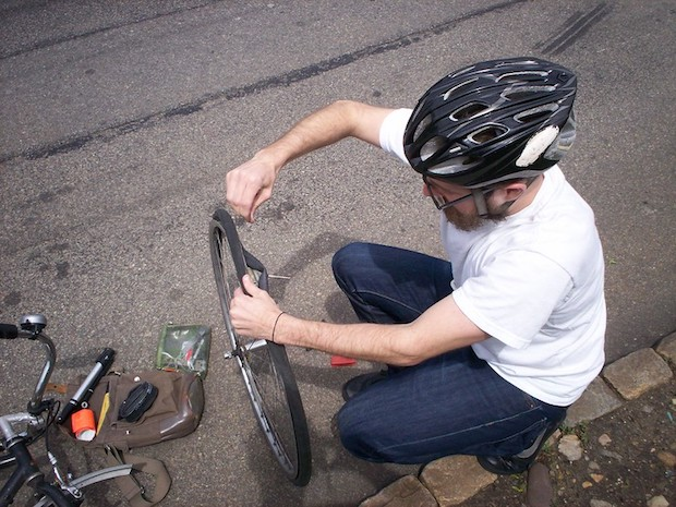 Cyclist fixing his flat tire at the side of the road