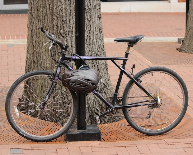 Locked bicycle with a helmet hanging from the frame