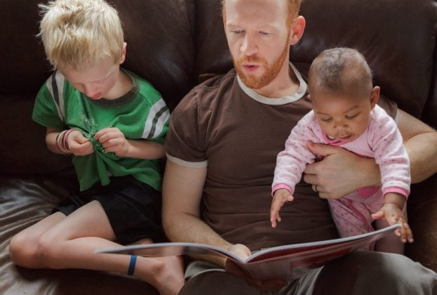 Father reading bedtime stories to his children - young son, and adopted african descent, multi-ethnic baby daughter.