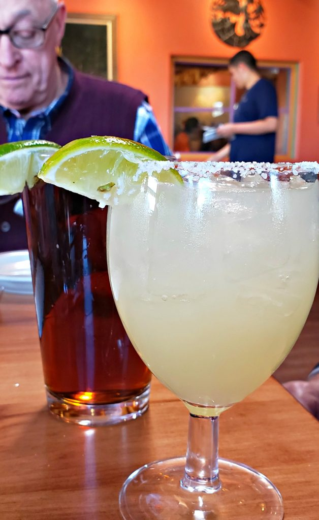 One of the best margarita santa fe sits next to a dark draft beer at La Choza restaurant