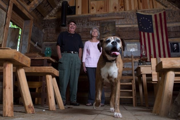 Joyce Lott, WC '59, right, her husband, Tom, and their dog Chloe pose for a photo inside the church and one-room schoolhouse at the village on their farm in Cleveland, Ga. (AJ Reynolds/Brenau University)