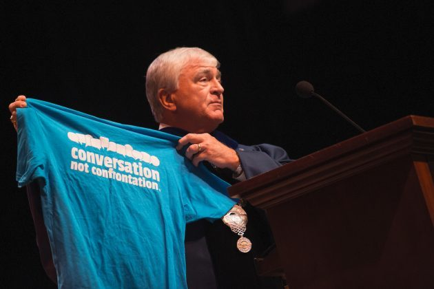 "Dr. Schrader holds blue t-shirt with white text that reads ""Conversation not Confrontation."""