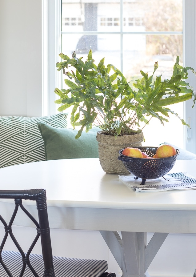 white breakfast nook table with green pillows