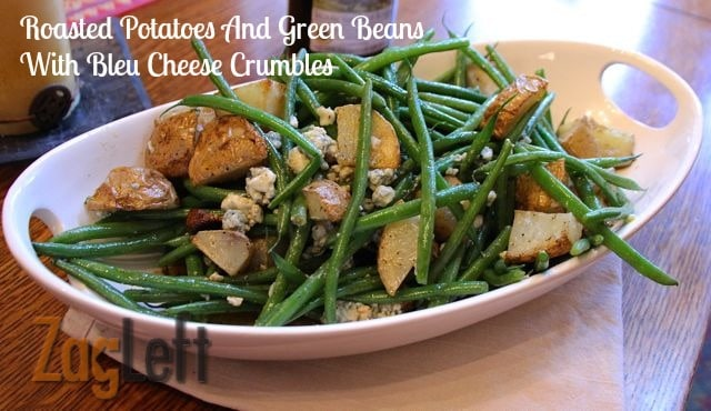 Roasted Potatoes and Green Beans topped with Bleu Cheese Crumbles in an oval serving dish on a wooden surface