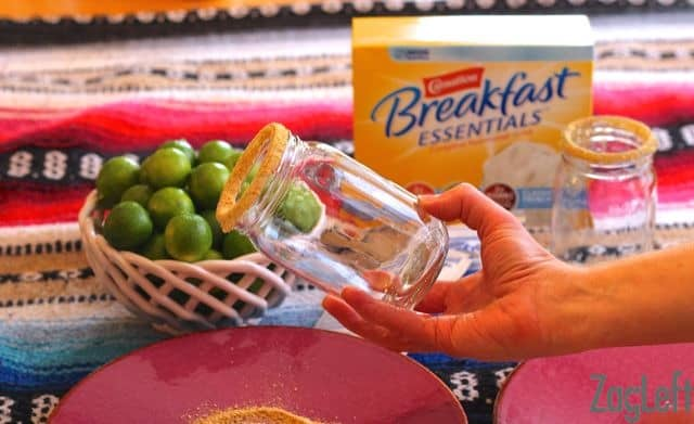 Showing a glass with a coated rim of graham cracker crumbs with a bowl of key limes and a box of Carnation Breakfast Essentials in the background