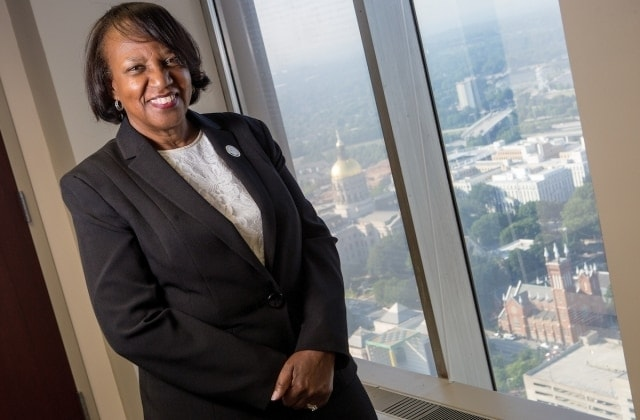 LaSharn Hughes, executive director of the Georgia Board for Physician Workforce, BU '98, BU '04 poses for a photo with the Georgia State Capital in the background at her office in Atlanta. (AJ Reynolds/Brenau University)