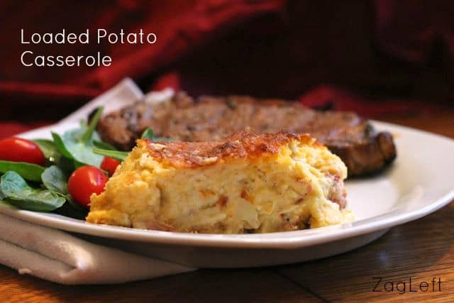 A slice of Loaded Potato Casserole on a plate with a steak and a side salad of spinach and cherry tomatoes