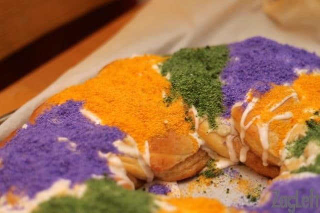 Closeup of King Cake topped with white glaze and yellow, green, and purple sanding sugar