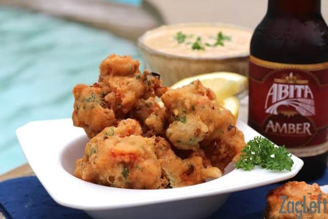 A bowl of Crawfish Beignets next to a glass of Remoulade Sauce and a bottle of beer with a pool in the background