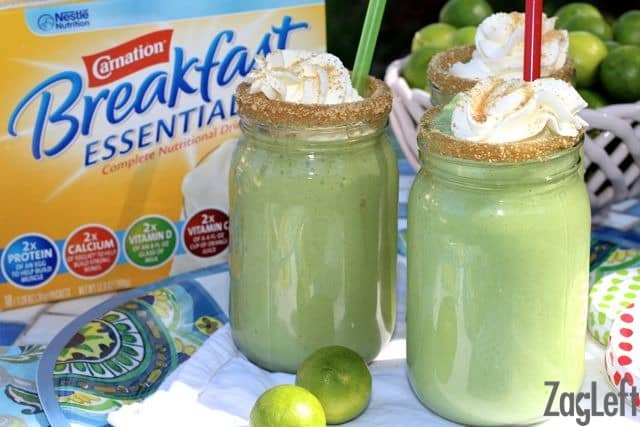 Three Key Lime Pie Smoothies with straws, crushed graham cracker crumbs on the rim, and topped with whipped cream and more graham cracker crumbs on a tray next to a bowl of key limes and a box of Carnation Breakfast Essentials