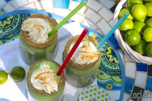 Overhead view of Three Key Lime Pie Smoothies with straws, crushed graham cracker crumbs on the rim, and topped with whipped cream and more graham cracker crumbs on a tray next to a bowl of key limes