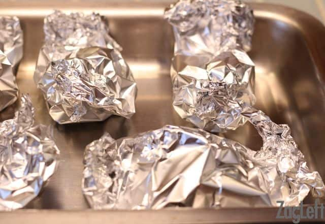 Five garlic heads wrapped individually in aluminum foil in a baking pan