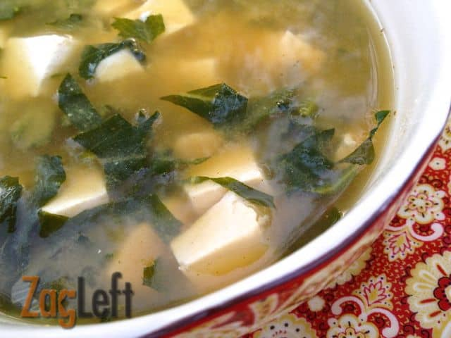 A closeup of a bowl of miso soup with tofu and kale