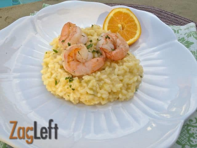 Overhead view of Orange Risotto topped with three pieces of Shrimp on a plate garnished with an orange wheel