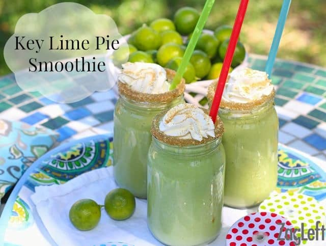 Three Key Lime Pie Smoothies with straws, crushed graham cracker crumbs on the rim, and topped with whipped cream and more graham cracker crumbs on a tray next to a bowl of key limes