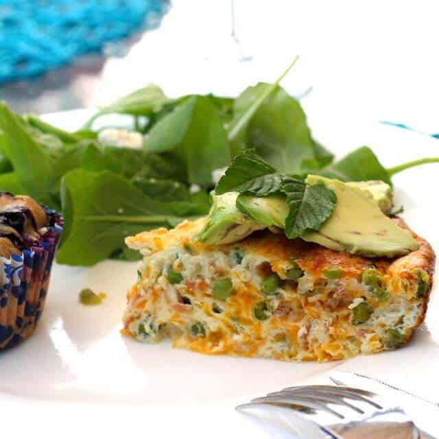 A slice of Pea, Cheddar and Crispy Pancetta Crustless Quiche topped with thin avocado slices with a spinach side salad and a blueberry muffin on a large plate
