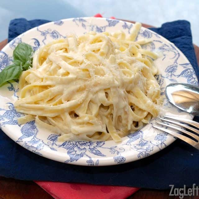 A plate of pasta with Alfredo sauce topped with parmesan cheese with a fork and spoon resting on the side of the plate