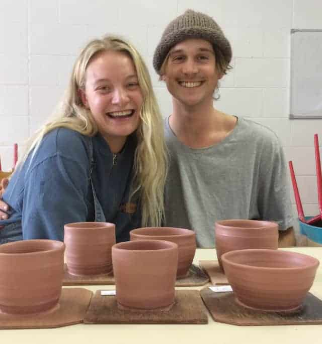 Private pottery lesson recipients happily displaying the finished product - greenware pottery bowls and mugs.