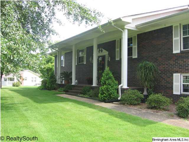 Brick home with 4 white columns on front porch, with green front yard and sidewalk.