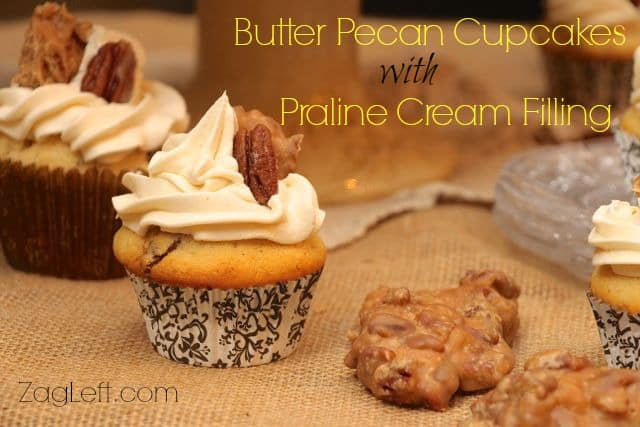 Two Butter Pecan Cupcakes with Praline Cream Filling topped with white icing, a piece of a praline, and a pecan next to two pralines on a burlap fabric