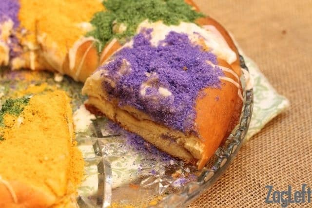 A slice taken out of a King Cake that is drizzled with white icing and topped with purple, green, and yellow sanding sugar