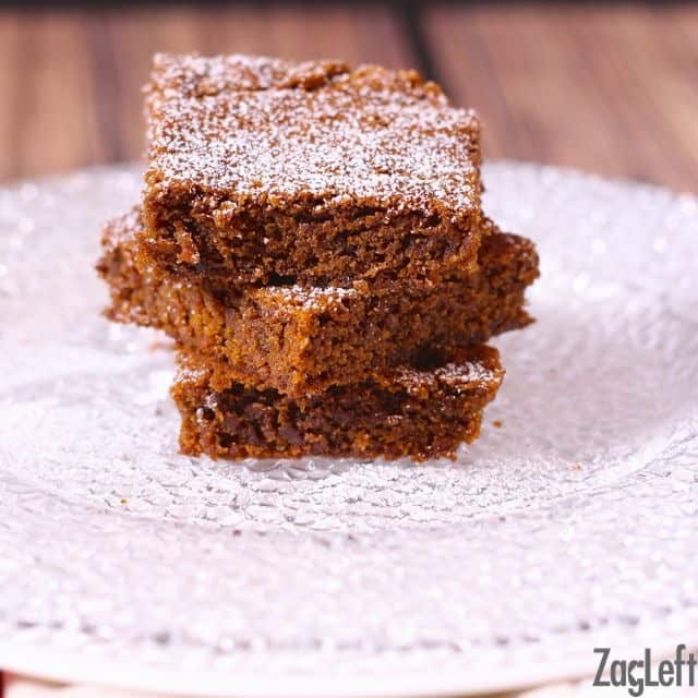 Three squared Gingerbread Bars dusted with powered sugar and stacked on a small plate