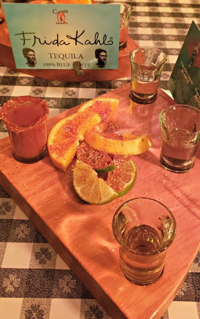 Three shot glasses of tequila sit on diamond-shaped board with a shot glass of tomato juice with spiced salt rim