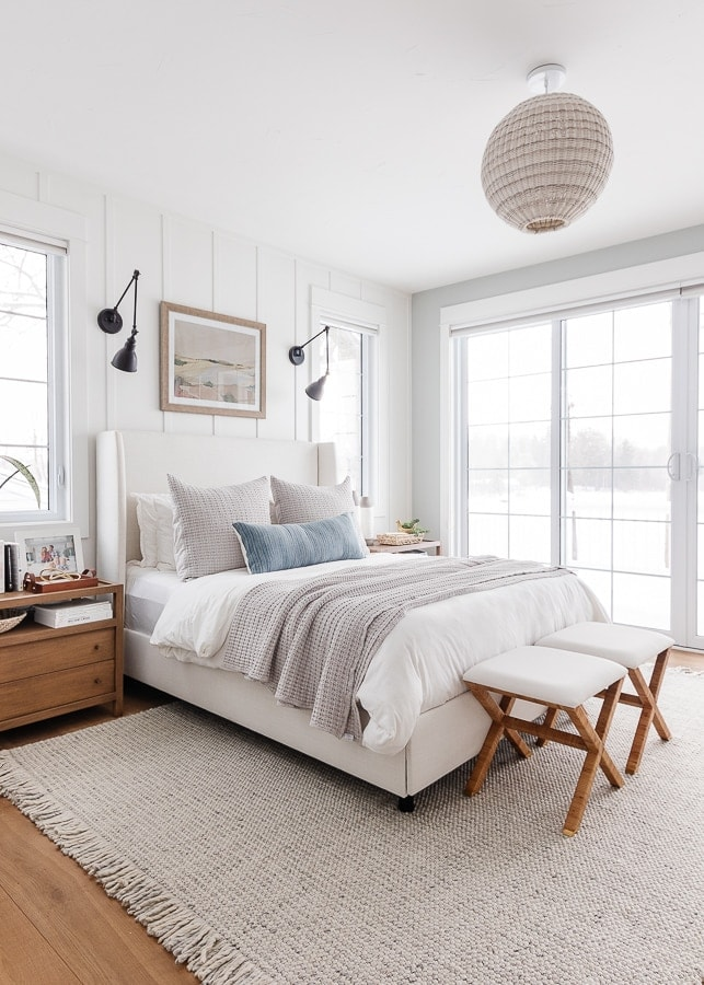lake house bedroom. White walls, neutral bedding, warm wood floors.