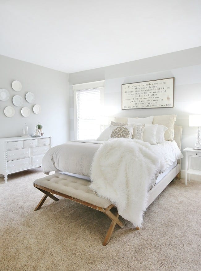 An upgraded white and gray farmhouse bedroom with gray walls and bright lighting with farmhouse decorations
