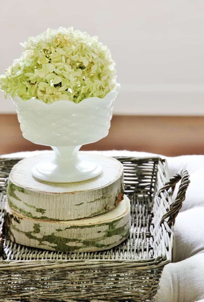 This delicate vase of hydrangeas contrasts well with the rustic pieces of wood.