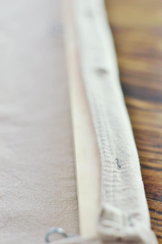 Continue by stapling the drop clothes to the pine wood boards.