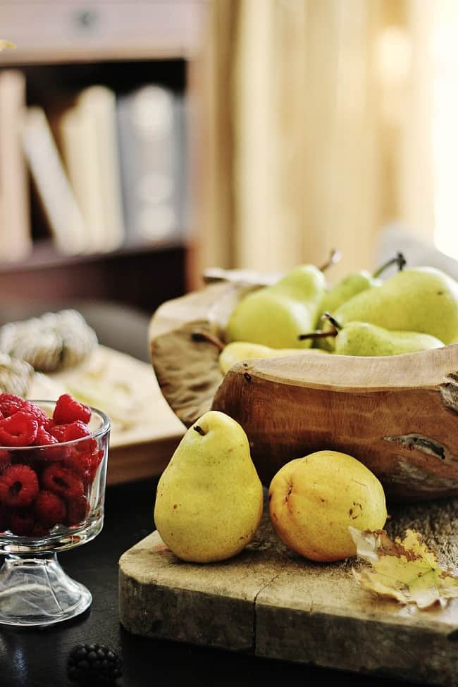 Displaying fresh fruit in big wooden pieces with scattered leaves creates a festive table.