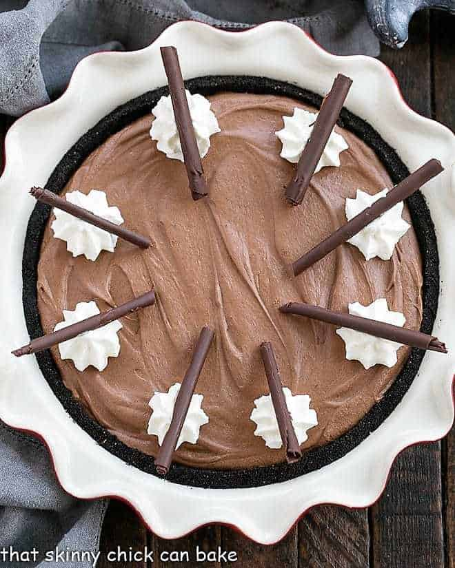 Frangelico French Silk Pie in a red ceramic pie plate with whipped cream and chocolate curl garnishes