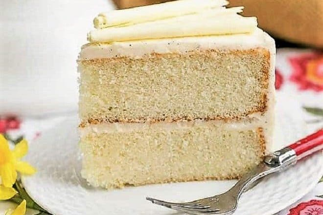 Slice of white birthday cake on a white dessert plate with a red handled fork