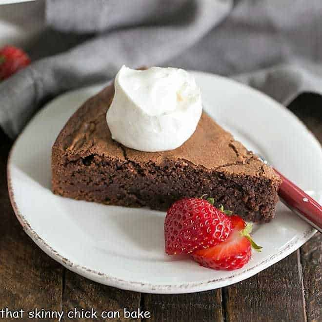 Italian Flourless Chocolate Cake with a dollop of cream, berries and a fork