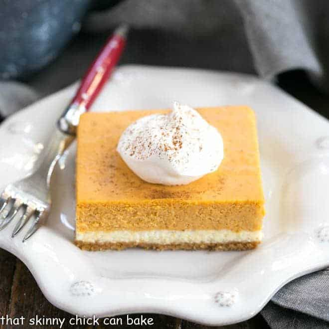 A slice of Layered Pumpkin Cheesecake Bars topped with whipped cream