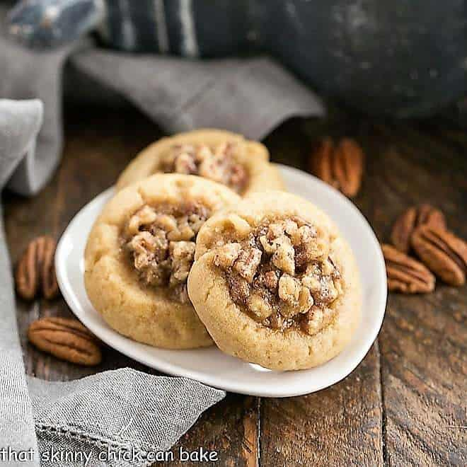 Pecan pie thumbprint cookies on a white ceramic plate