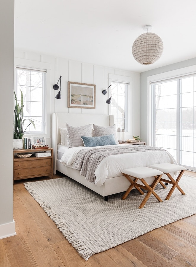 white paneled walls with blue paint. White bedding with gray rug and throw pillows. Coastal bedroom decor