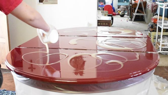 Lighter epoxy colors being added in swirling pattern to red-tinted epoxy layer.