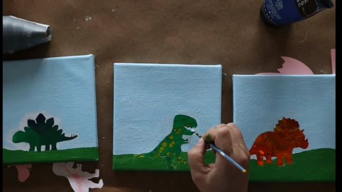 painting the details of the background in of the dinosaur painting
