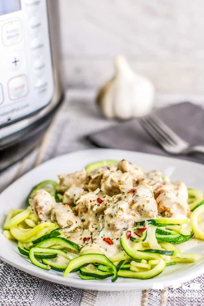 instant pot creamy garlic chicken over zoodles on white plate