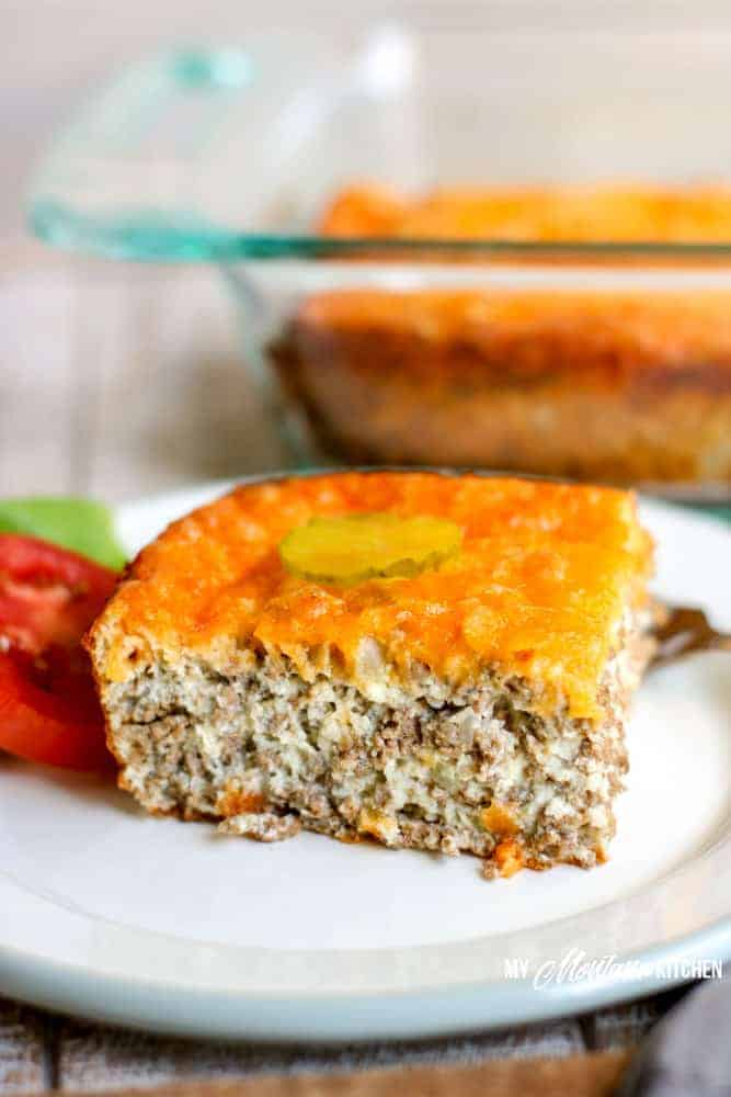 low carb cheeseburger pie on white plate with tomato lettuce and pickle