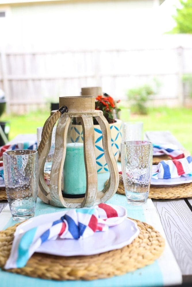 Patio table set with white plates and wood decor