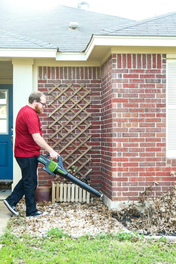 man blowing leaves in yard