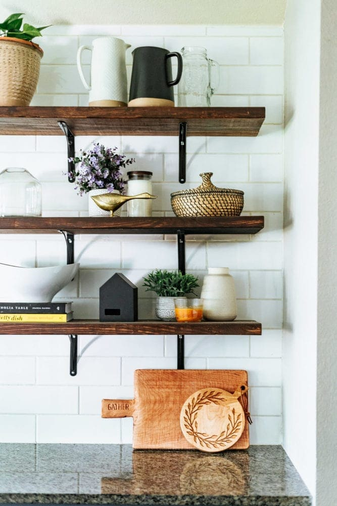 floating shelves in kitchen with two bread boards sitting on counter