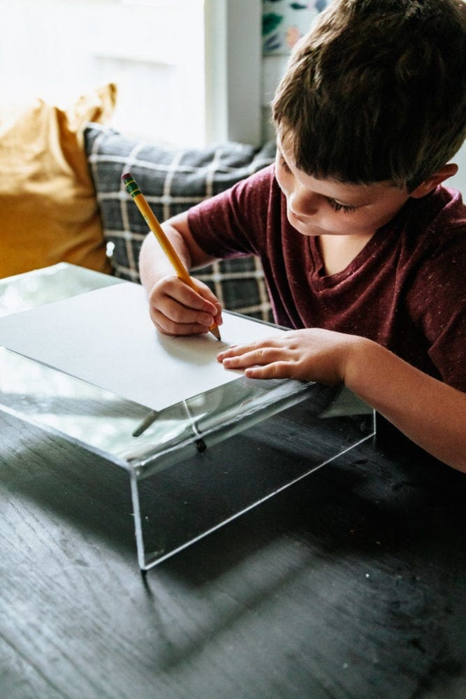 close up of a young boy coloring on an acrylic lap desk