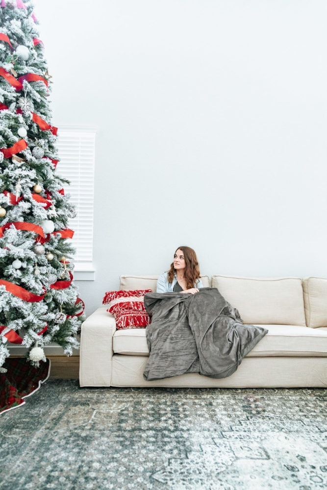 woman on a couch with a Tranquility weighted blanket