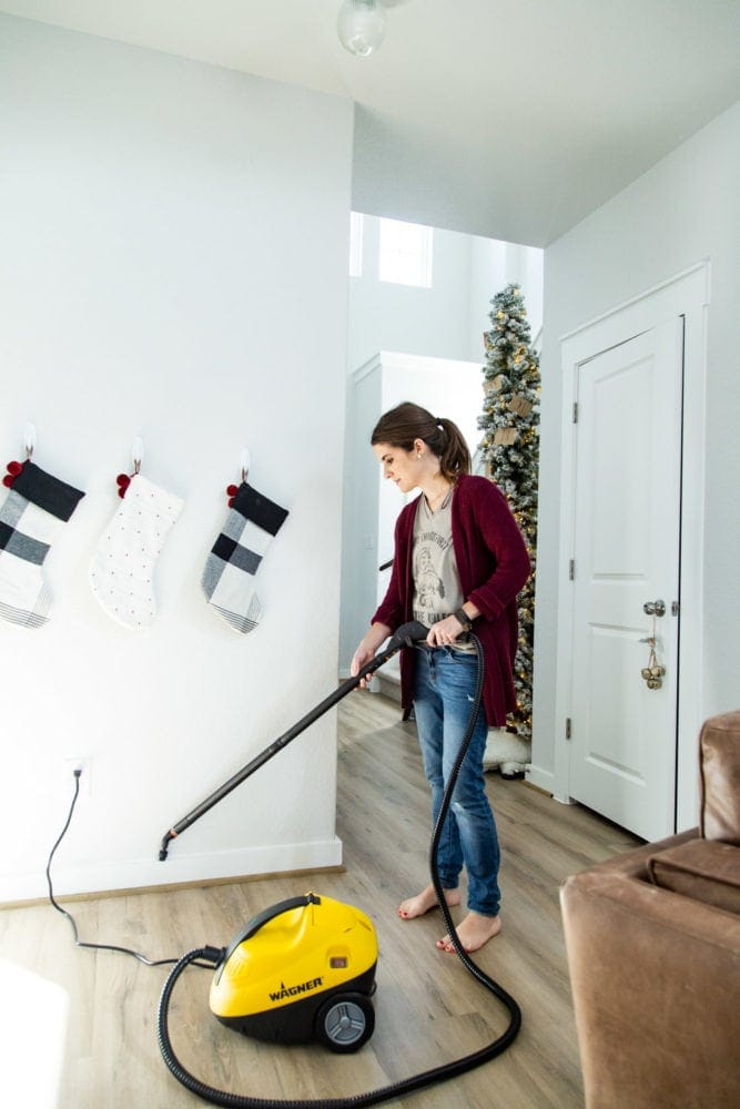 woman cleaning baseboards using a steamer